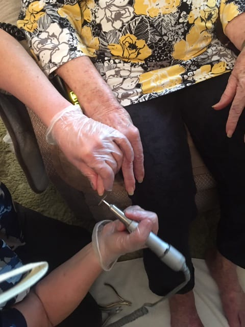 registered nurse performing nail care on a Covenant Home Care client